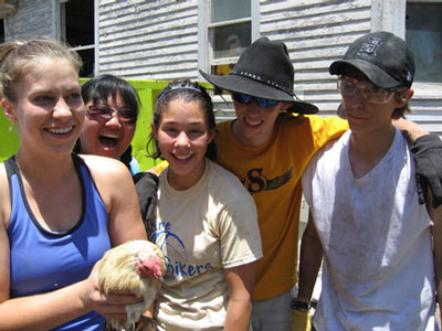 Members of the Saline Fiddlers with a rooster they rescued in Biloxi, Mississippi